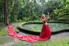 Fairy tale 4. Beautiful girl in a red long dress standing in the enchanted forest near waterpool and resists wind. Fabulous witch reads the spell Royalty Free Stock Photo