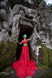 Fairy tale 2. Beautiful girl stands at the entrance to the ancient cave with frightening mask. Bali mask Stock Photos