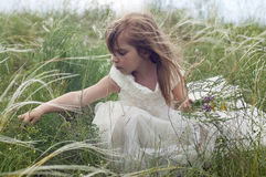 Fairy-tale beautiful little girl on a lawn Royalty Free Stock Image
