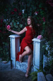 Fairy tale. Beautiful princess in red dress sitting in a mystical garden Royalty Free Stock Image
