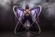 Fairy-tale character assassin in a purple cloak with a hood with two large cyr wheel hoops. Fairy-tale character assassin in a purple cloak with a hood with two Royalty Free Stock Photography