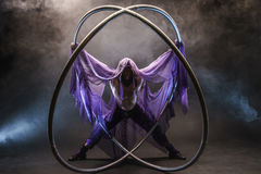Fairy-tale character assassin in a purple cloak with a hood with two large cyr wheel hoops Royalty Free Stock Image