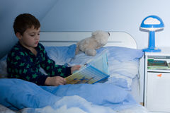 Fairy tale. Cute little boy reading a fairy tale in bed Royalty Free Stock Images