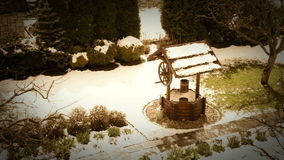 A fairy-tale footage of an old-fashioned decorative well standing in the yard with snow falling