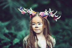 Fairy tale girl. Portrait a little girl in a deer dress with a painted face in the forest. Big brown antler. Fantasy girl stock photos