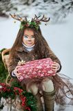 Fairy tale girl. Portrait a little girl in a deer dress with a painted face in the winter forest. Big brown antler stock photography