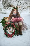 Fairy tale girl. Portrait a little girl in a deer dress with a painted face in the winter forest. Big brown antler stock photos