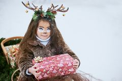 Fairy tale girl. Portrait a little girl in a deer dress with a painted face in the winter forest. Big brown antler stock images