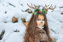 Fairy tale girl. Portrait a little girl in a deer dress with a painted face in the winter forest. Big brown antler. Fantasy girl with christmas bells. Snowy royalty free stock photography
