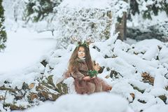 Fairy tale girl. Portrait a little girl in a deer dress with a painted face in the winter forest. Big brown antler. Fantasy girl with christmas bells. Snowy stock photos