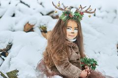 Fairy tale girl. Portrait a little girl in a deer dress with a painted face in the winter forest. Big brown antler. Fantasy girl with christmas bells. Snowy stock images