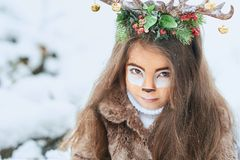 Fairy tale girl. Portrait a little girl in a deer dress with a painted face in the winter forest. Big brown antler. Fantasy girl with christmas bells. Snowy stock photography