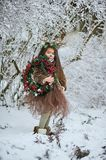 Fairy tale girl. Portrait a little girl in a deer dress with a painted face in the winter forest. Big brown antler. Fantasy girl with christmas wreath. Snowy stock photos