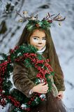 Fairy tale girl. Portrait a little girl in a deer dress with a painted face in the winter forest. Big brown antler. Fantasy girl with christmas wreath. Snowy stock images