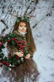 Fairy tale girl. Portrait a little girl in a deer dress with a painted face in the winter forest. Big brown antler. Fantasy girl with christmas wreath. Snowy stock image