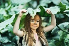 Fairy tale girl. Portrait a little girl in a deer dress with a painted face in the forest. Big antler. Fantasy girl. Springtime. stock photos