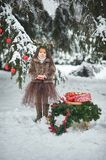 Fairy tale girl. Portrait a little girl in a deer dress with a painted face in the winter forest. Big brown antler royalty free stock images