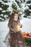 Fairy tale girl. Portrait a little girl in a deer dress with a painted face in the winter forest. Big brown antler. Fantasy girl with christmas bells. Snowy royalty free stock photos