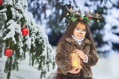 Fairy tale girl. Portrait a little girl in a deer dress with a painted face in the winter forest. Big brown antler. Fantasy girl with christmas bells and royalty free stock photo
