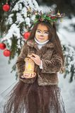 Fairy tale girl. Portrait a little girl in a deer dress with a painted face in the winter forest. Big brown antler. Fantasy girl with christmas bells and stock images