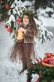Fairy tale girl. Portrait a little girl in a deer dress with a painted face in the winter forest. Big brown antler. Fantasy girl with christmas bells and royalty free stock photos