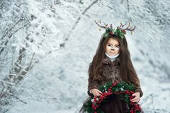 Fairy tale girl. Portrait a little girl in a deer dress with a painted face in the winter forest. Big brown antler. Fantasy girl with christmas wreath. Snowy royalty free stock photography