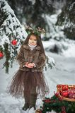 Fairy tale girl. Portrait a little girl in a deer dress with a painted face in the winter forest. Big brown antler. Fantasy girl with christmas bells. Snowy royalty free stock images