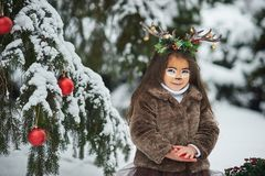 Fairy tale girl. Portrait a little girl in a deer dress with a painted face in the winter forest. Big brown antler. Fantasy girl with christmas bells. Snowy stock photo