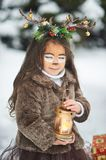 Fairy tale girl. Portrait a little girl in a deer dress with a painted face in the winter forest. Big brown antler. Fantasy girl with christmas bells and stock photography