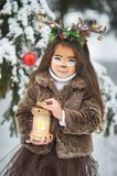 Fairy tale girl. Portrait a little girl in a deer dress with a painted face in the winter forest. Big brown antler. Fantasy girl with christmas bells and stock image