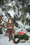Fairy tale girl. Portrait a little girl in a deer dress with a painted face in the winter forest. Big brown antler. Girl carries a Christmas tree and presents stock images