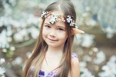 Fairy tale girl. Portrait of mystic elf child. Cosplay character. Portrait of an elf in a blooming magnolia garden. A girl with long ears touches the flowers stock image
