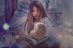 Fairy tale girl. Fairy tale reading little girl in the dark royalty free stock photography