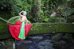Fairy Tale. Girl in a red dress sitting on the old stone bridge Royalty Free Stock Photos