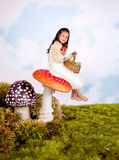 Fairy tale girl on toadstool. Cute little girl sitting on a toadstool in a fairytale stock photos