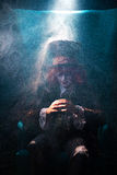 The fairy-tale hatter in the smoke. A fairy-tale hatter sits cross-arms in smoke Royalty Free Stock Images