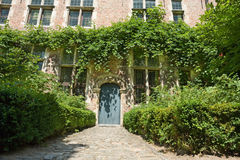 Fairy tale medieval house entry. Facade and overgrown entry and fa�ade of a medieval Flemish house in the Louvain (Belgium) beguinage. Entry path with Stock Images