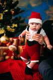 Fairy-tale portrait of Christmas cute little baby wearing like santa claus at the new year background under tree Royalty Free Stock Photos