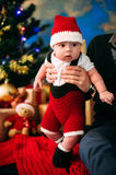 Fairy-tale portrait of Christmas cute little baby wearing like santa claus at the new year background under tree Royalty Free Stock Image