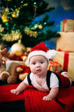 Fairy-tale portrait of Christmas cute little baby wearing like santa claus at the new year background under tree Stock Image