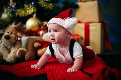 Fairy-tale portrait of Christmas cute little baby wearing like santa claus at the new year background under tree Stock Photos