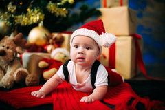 Fairy-tale portrait of Christmas cute little baby wearing like santa claus at the new year background under tree. Fairy-tale portrait of Christmas baby on winter Royalty Free Stock Photos