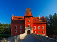 Fairy tale red castle on the lake with bridge, with dark blue sky, state castle Cervena Lhota, Czech republic. Fairy tale red castle on the lake with bridge Royalty Free Stock Images