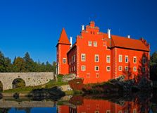 Fairy tale red castle on the lake, with dark blue sky, state castle Cervena Lhota, Czech republic. Fairy tale red castle on the lake, with dark blue sky, state Stock Photo