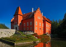 Fairy tale red castle on the lake, with dark blue sky, state castle Cervena Lhota, Czech republic. Fairy tale red castle on the lake, with dark blue sky Stock Photography