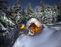 Fairy-tale snow-covered house in the mountains stock images