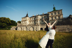 Fairy-tale wedding couple handsome groom swinging beautiful brid Royalty Free Stock Photography
