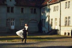 Fairy-tale wedding couple handsome groom swinging beautiful brid Stock Photos
