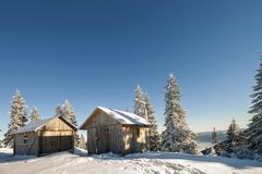 Fairy tale winter sunny landscape. Two weathered wooden shepherd royalty free stock photography