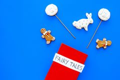 Fairy tales book near gingerbread man and candies on blue background top view copy space stock image